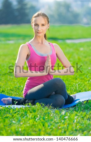 Beautiful sport woman doing stretching fitness exercise in city park at green grass. Yoga postures
