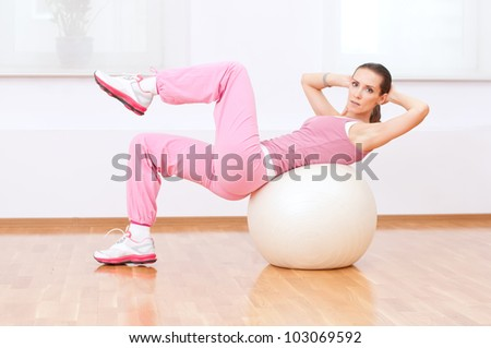 Beautiful sport woman doing stretching fitness exercise on ball at sport gym