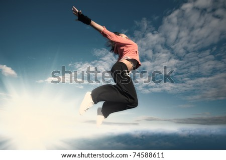 Beautiful sport woman in urban sportswear jumping and fly over blue sky with clouds and sun beam - stock photo