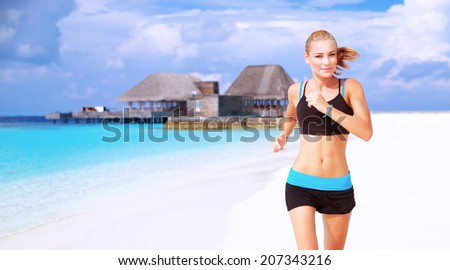 Beautiful sportive female running on the beach, workout on luxury Maldives resort, doing fitness exercises outdoors, healthy lifestyle, active summer vacation concept - stock photo