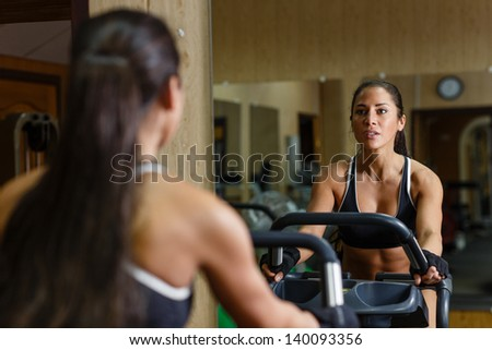Beautiful sports woman exercising on the bicycle in the gym. - stock photo