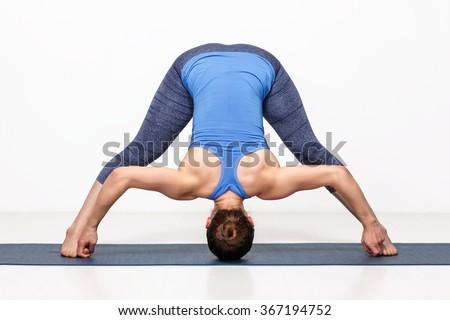 Beautiful sporty fit woman practices Ashtanga Vinyasa yoga asana Prasarita padottanasana D - wide legged forward bend D - stock photo