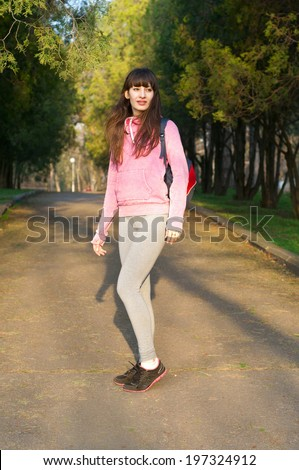 Beautiful sporty fit woman with pretty strong legs, wearing gray tights, pink hoodie, with a backpack walking in a park. On a bright sunny spring day - stock photo