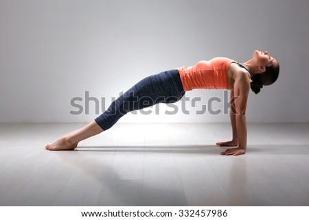Beautiful sporty fit yogini woman practices Ashtanga Vinyasa yoga asana Purvottanasana - upward-facing plank full pose - stock photo