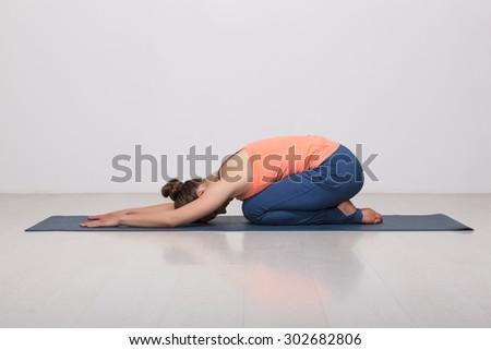 Beautiful sporty fit yogini woman practices yoga asana balasana (child's pose) - resting pose or counter asana for many asanas in studio - stock photo
