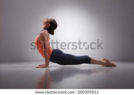 Beautiful sporty fit yogini woman practices yoga asana urdhva mukha svanasana - upward facing dog pose in studio - stock photo