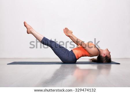 Beautiful sporty fit yogini woman practices yoga asana Uttana padasana - raised legs pose - stock photo