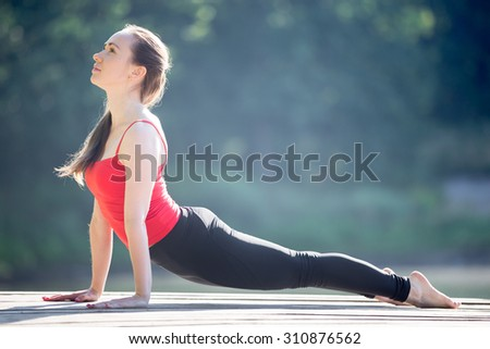 Beautiful sporty fit young woman in sportswear working out outdoors on summer day, doing exercise for back, urdhva mukha shvanasana (upward facing dog posture), full length, side view - stock photo