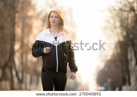 Beautiful sporty girl in sportswear walking in earphones the morning street, healthy active lifestyle concept - stock photo