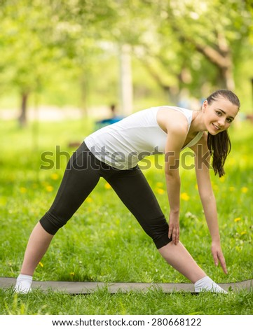 Beautiful sporty girl stands on the mat in park and stretching.