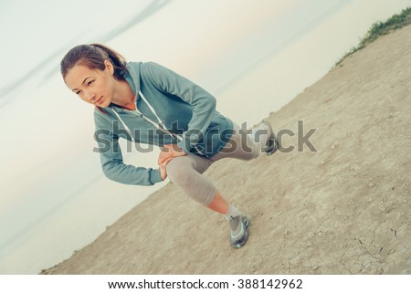 Beautiful sporty girl stretching her legs and preparing to run on coast in summer in the morning, workout. Concept of healthy lifestyle