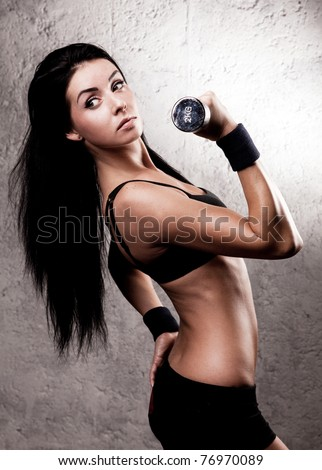 beautiful sporty muscular woman with a dumbbell in the gym - stock photo