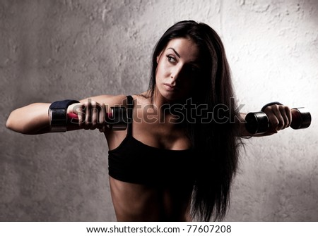 beautiful sporty muscular woman with two dumbbell in the gym - stock photo