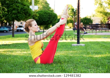Beautiful sporty woman doing yoga exercise outdoors. Full boat pose. - stock photo