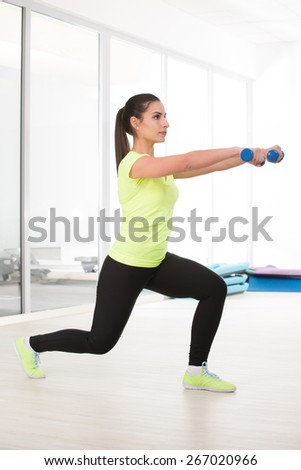Beautiful sporty woman in yellow t-shirt make sit with dumbbell in gym - stock photo