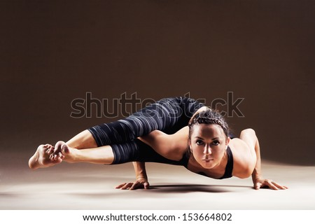 Beautiful sporty woman is working out. Eight-angle pose, Astavakrasana - stock photo