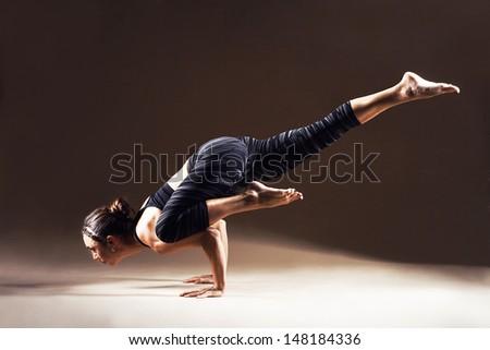 Beautiful sporty woman is working out. Galavasana. - stock photo