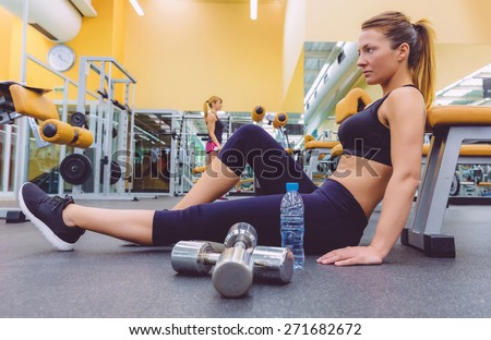 Beautiful sporty woman resting sitting on the floor of fitness center and female friend doing exercises with dumbbells in the background - stock photo
