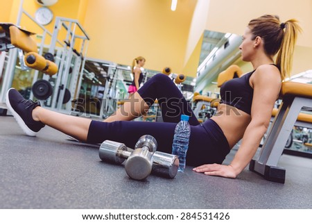 Beautiful sporty woman resting sitting on the floor of fitness center and female friend doing exercises with dumbbells in the background. Selective focus on a dumbbles and bottle water. - stock photo