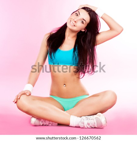 beautiful sporty woman stretching the muscles of her neck and back against pink studio background