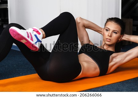 beautiful sporty woman woman doing exercises, pumping a press - stock photo