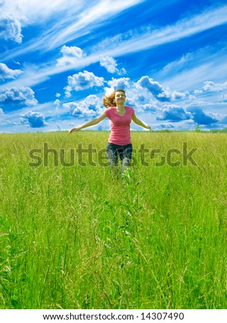 beautiful spreading her arms in the middle of a field