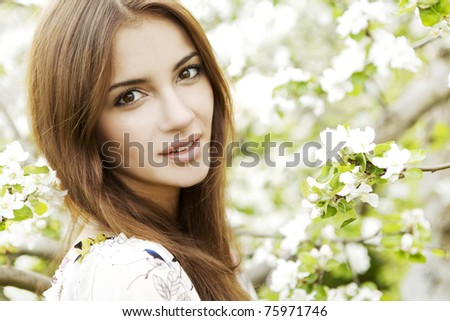 Beautiful Spring Brunette Girl with flowers - stock photo