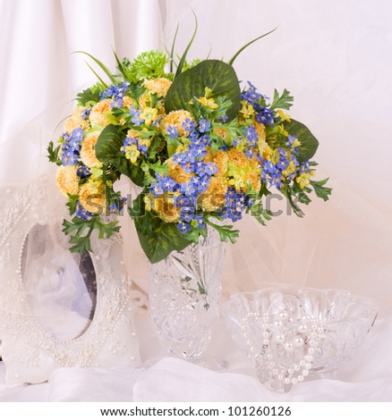 Beautiful spring flowers in a glass vase and frame on background