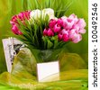 Beautiful spring flowers in a glass vase with banner add - stock photo