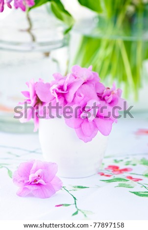 Beautiful spring flowers in a vase on light background - stock photo