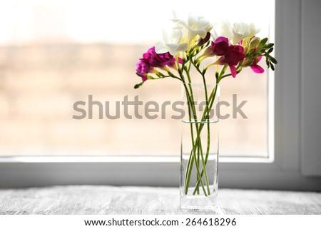 Beautiful spring flowers in glass vase on windowsill background - stock photo