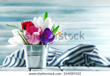 Beautiful spring flowers in metal bucket on color background - stock photo