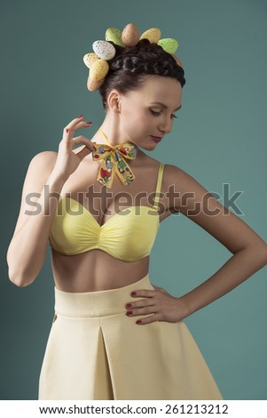 Beautiful, spring, funny woman in yellow dress, top and little cute loop on the neck. She has got funny egg hairstyle and nice nude make up. - stock photo