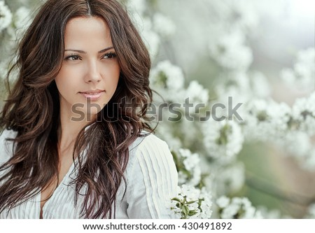 Beautiful spring girl in blooming tree - stock photo