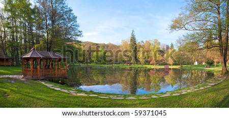 Beautiful spring lake and wooden belvedere in the park. Two shots stitch image.