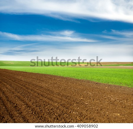 Beautiful spring landscape with plowed field under blue sky with clouds - stock photo