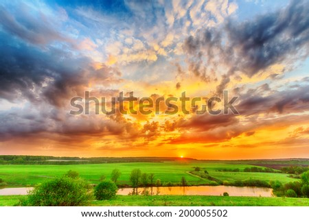 Beautiful spring sunset over pond on the plain - stock photo