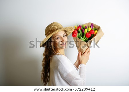 Beautiful spring woman in a hat holding a bouquet of colorful spring flowers. The concept of International Women's Day