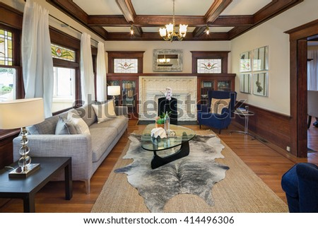 Beautiful staged living room in classic craftsman house with, couch, fire place, blue chairs and glass table.  - stock photo