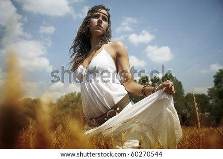 Beautiful standing in the middle of a wheat field on a hot summer afternoon. Dressed in white and feeling the nature. - stock photo