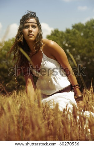 Beautiful standing in the middle of a wheat field on a hot summer afternoon. Dressed in white and feeling the nature.