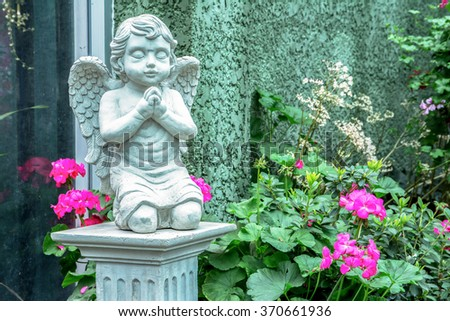 Beautiful statue of the angel praying in the park - stock photo