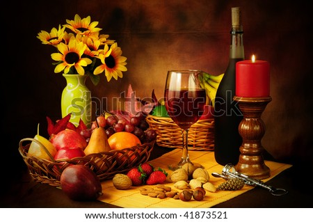 Beautiful still life image of red wine, fruits and nuts with dramatic lighting - stock photo