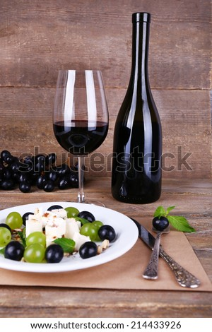 beautiful still life with wine and salad on wooden background - stock photo