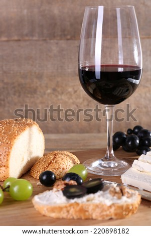 beautiful still life with wine, cheese and ripe grape on wooden background - stock photo