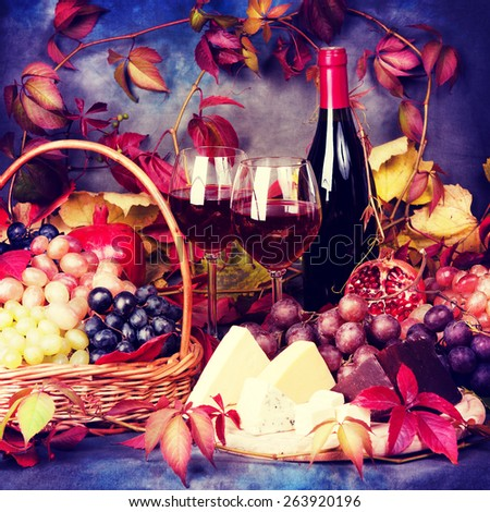 Beautiful still life with wine glasses, grapes, pomegranate and cheese. Vintage retro hipster style version - stock photo