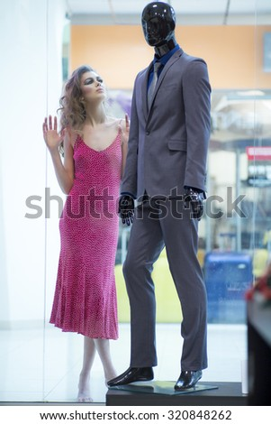 Beautiful straight slim young sensual blonde woman model with bright makeup and curly hair in red dress standing barefoot near mannequin in grey suit on shop background, vertical - stock photo
