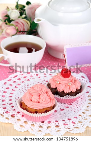 Beautiful strawberry cupcakes and flavored tea on dining table close-up