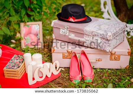 beautiful strawberry wedding accessories with shoes, hat, LOVE word and vintage suitcases - stock photo