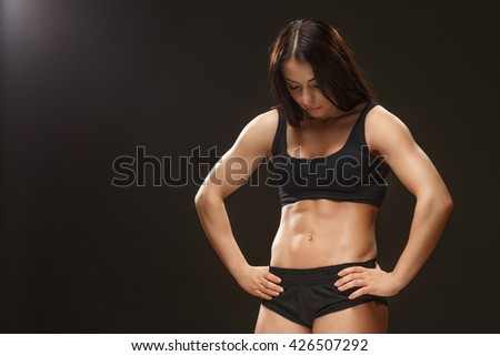 Beautiful strength. Studio portrait of a sporty female athlete wearing black top and shorts posing showing off her abs copyspace on the side against black background. - stock photo